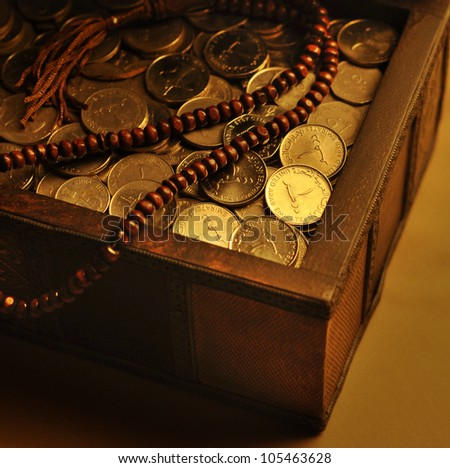 UAE Dirham coins in a trunk and wooden rosary - stock photo
