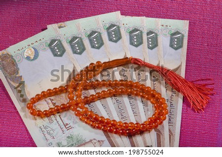 UAE dirham currency notes and a rosary - sharia finance objects - stock photo