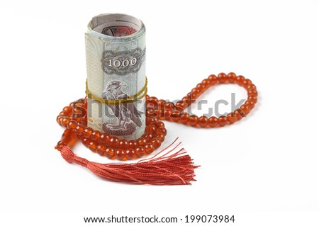 UAE dirham notes rolled with rosary - stock photo