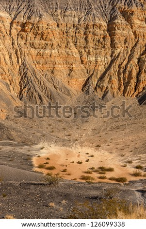 "Ubehebe Crater. ""Ubehebe""  is a Timbisha Native American word meaning ""Big basket in the rock."" Miocene-aged mostly reddish orange-colored conglomerate makes up the exposed bedrock in the walls. - stock photo"