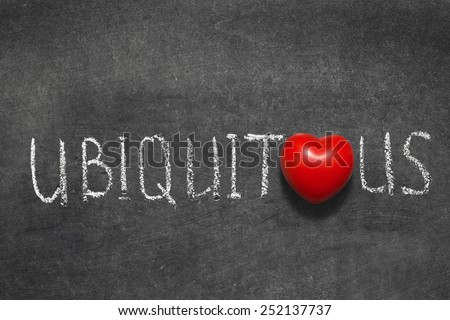 ubiquitous word handwritten on blackboard with heart symbol instead of O