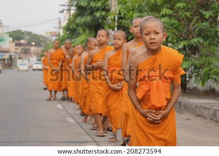 Ubon Ratchathani, Thailand - April 2, 2013: Little monks of Thung Sri Muang temple were walking to another temple to study Buddhism lesson.