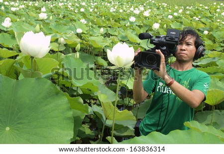 UBON RATCHATHANI, THAILAND - OCT 14, 2013 : Unidentified man taking video recorder in lotus farm as reporter for organic agriculture documentary on Oct 14, 2013 in Detudom, Ubon Ratchtahni, Thailand. - stock photo