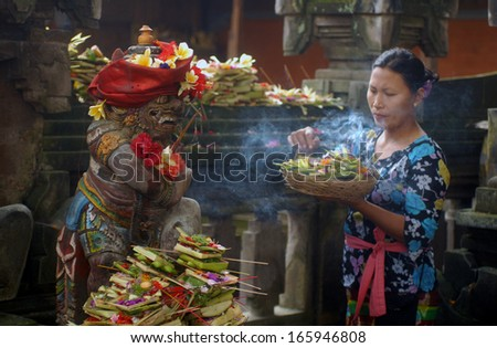 UBUD, BALI, INDONESIA - FEBRUARY,14: a woman offers flowers to goddess, on February,14, 2005 in Ubud, Bali, Indonesia. - stock photo