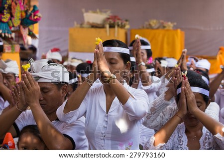 UBUD, BALI, INDONESIA - MARCH 25, 2015 : Unidentified Indonesian people celebrate Balinese New Year. Women and men pray in the local temple - stock photo