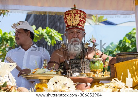 UBUD, BALI, INDONESIA - MARCH 19, 2015 : Unidentified Indonesian people celebrate Balinese New Year and the arrival of spring. Old Brahmin conducts religious ritual on the beach Ketewel - stock photo