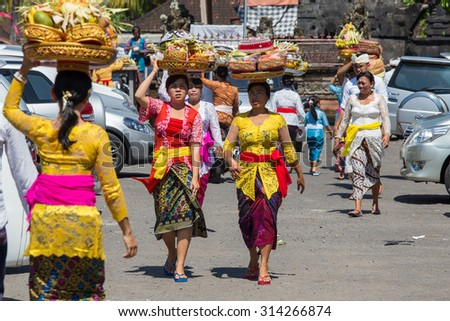 UBUD, BALI, INDONESIA - MARCH 19, 2015 : Unidentified Indonesian people celebrate Balinese New Year and the arrival of spring. Balinese women bring offerings of fruits and gifts to the village temple - stock photo