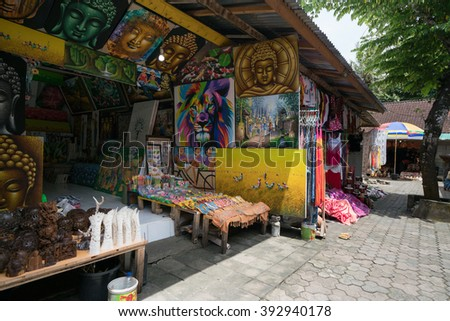 UBUD, BALI - MARCH 14, 2016: Colorful paintings from unknown local artists are for sale on at the souvenir market in Pura Tirta Empul (temple), Bali.  This temple is a major tourist attraction.