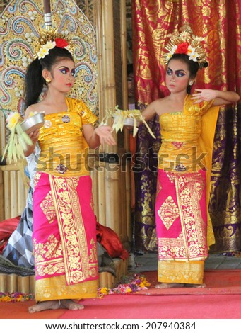 UBUD, INDONESIA-April 13: Two costumed dancers perform a traditional Balinese dance with elaborate makeup and costuming before an audience on April 13, 2014.  - stock photo