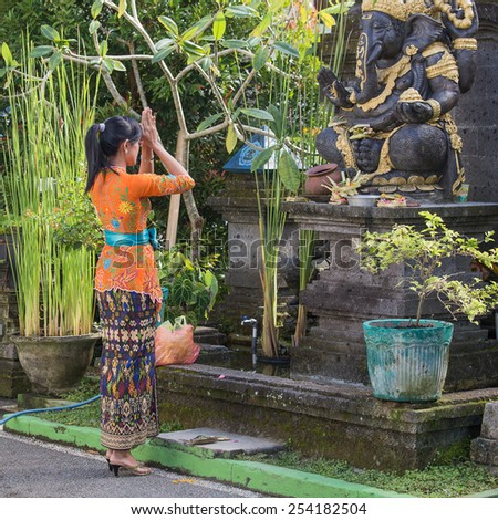 UBUD, INDONESIA - FEBRUARY 18, 2015 : Unknown young Balinese woman to pray before the statue of Ganesha - stock photo