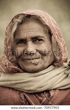 UDAIPUR, INDIA - CIRCA JANUARY 2007: An old Indian woman with traditional nose-ring smiles in the fields circa January 2007 in Udaipur, India. - stock photo