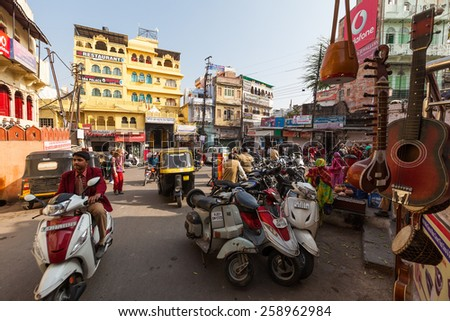 UDAIPUR, INDIA - JANUARY 16, 2015 : Busy street scene in Jagdish Chowk, a central town square in Udaipur filled with mopeds, rickshaws, locals, tourists, hotels, shops and restaurants. - stock photo