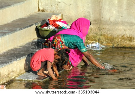 UDAIPUR, INDIA - NOVEMBER 23, 2012: Woman with her daughter washing clothes in lake