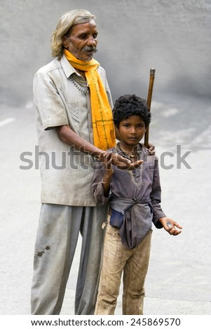 UDAIPUR, INDIA - SEPTEMBER 11: An unidentified blind man begging for money with the help of an young boy in the streets on September 11, 2008 in the streets of Udaipur, India - stock photo
