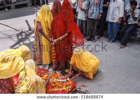 Udaipur, Rajasthan, India - August 19, 2012. Women dressed in traditional sari dresses, attend the funeral of an elderly woman, at the city of Udaipur, at the state of Rajasthan in north western India