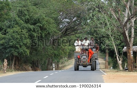 UDAWALAWE, SRI LANKA - FEBRUARY 22: A typical scene of local people including a monk using a tractor for transport on a main road outside of Udawalawe, Sri Lanka on the 22nd February, 2014.