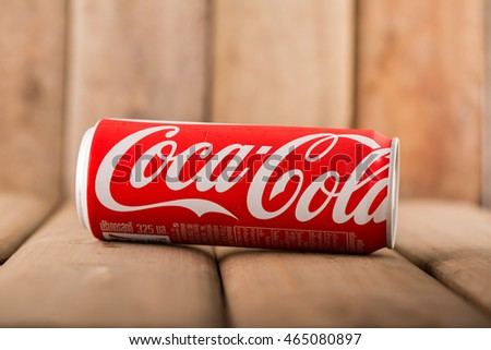 UDON THANI,THAILAND - August 7, 2016. Coca Cola can on wooden table. Coca Cola drinks are produced and manufactured by The Coca-Cola Company, an American multinational beverage corporation