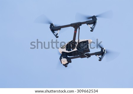 Udon Thani, Thailand, August 16, 2015: White drone, quadrocopter, with photo camera flying in the blue sky. Concept. Aircraft, remote unmanned aircraft.