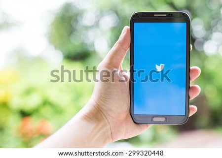 UDON THANI,THAILAND - July 24, 2015: man holding a brand samsung galaxy note 2 with Twitter logo on the screen. Twitter is a social media online service for microblogging and networking communication.