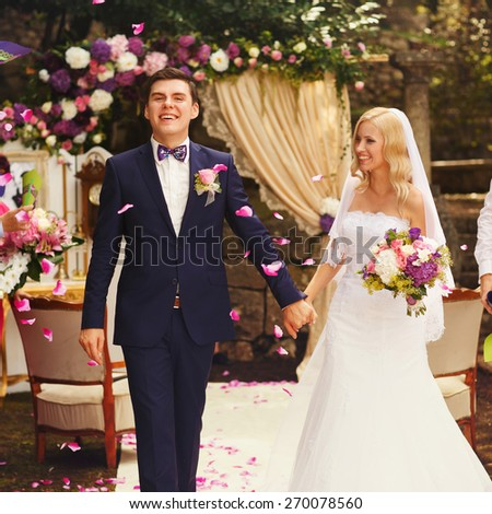 uests throw the petals on confetti on happy married bride and groom after the wedding ceremony - stock photo