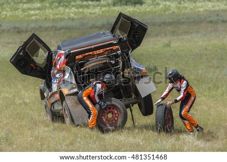 UFA, RUSSIA-JULY 11, 2016: The pilots change the damaged wheel during the  Silk Way rally Moscow-Beijing Dakar series on a dirt road