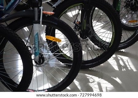 UFA, RUSSIA 22ND SEPTEMBER 2017 - Rows of front wheels and tires of bikes on display with black rubber wheels