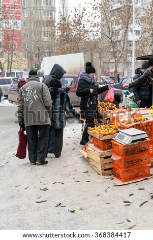UFA - RUSSIA 26TH DECEMBER 2015 - Tangerine sellers sell bright fresh fruits from their stall in the winter farmer's markets in Ufa, Russia 2015.