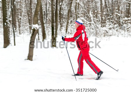 UFA - RUSSIA 5TH DECEMBER 2015 - Woman skier in bright red winter ski clothing exercises by cross country skiing a local public park in Ufa, Russia
