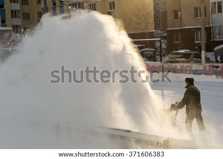 UFA - RUSSIA 17TH JANUARY 2016 - Manual worker uses a snow machine for help clearing snow from a public ice rink in Ufa, Russia in January 2016.
