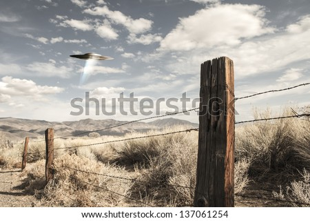 UFO spaceship in the high desert of California with an old fence post, mountains and clouds. - stock photo