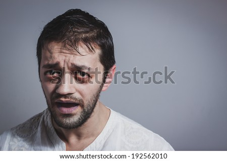 Ugly young bearded man looking sick on grey background - stock photo