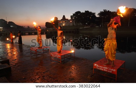 UJJAIN - INDIA - JANUARY 5, 2016: Unidentified Hindu priests performing a religious aarti on January 5, 2016 in Ujjain, India. Ujjain will host the world-famous Hindu pilgrimage Kumbh Mela in Mai 2016 - stock photo