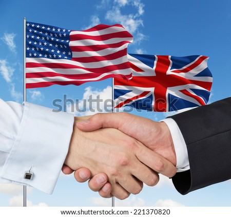 UK and US flags with a handshake on a blue sky background. - stock photo
