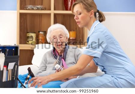 UK nurse visiting senior woman at home - stock photo