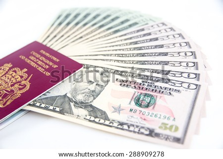 UK Passport holding a fan of US Dollars