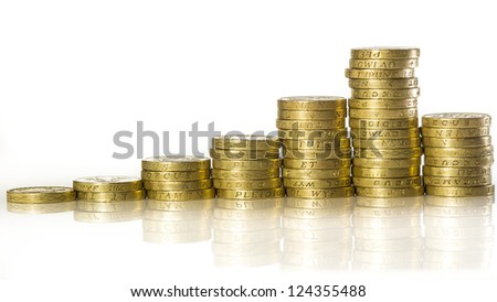 Uk pound coins stacked on white background with a reflection - stock photo
