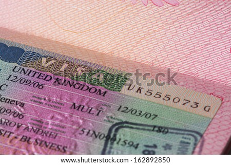 UK visa in passport, closeup - stock photo