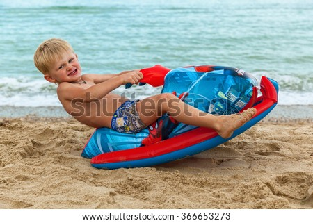 Ukraine Black Sea August 10, 2015: A boy playing on the beach with children's inflatable watercraft August 10, 2015 Ukraine Black Sea