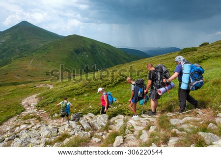 Ukraine. Carpathian mountains. A group of tourists with backpacks on the mountain while a thunderstorm approaches.