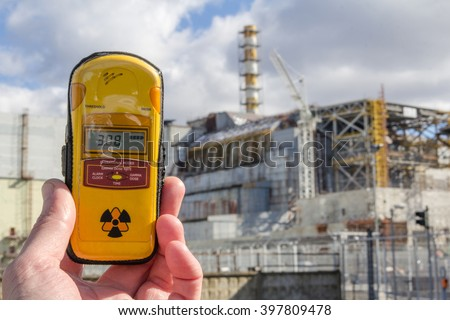 UKRAINE. Chernobyl Exclusion Zone. - 2016.03.19. Dosimeter and Nuclear Power Plant on the background - stock photo