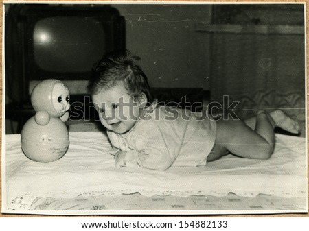 UKRAINE - CIRCA 1967: An antique photo shows girl lying on her stomach on the bed, next is roly-poly, Voroshilovgrad, now Lugansk,  1967