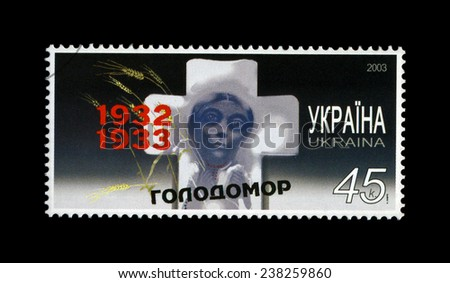 UKRAINE - CIRCA 2003: cancelled stamp printed in Ukraine shows famine (starvation) of 1932-33 in Ukraine, circa 2003. vintage post stamp isolated on black background.  - stock photo