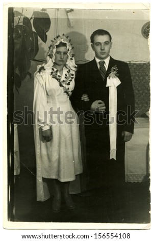 UKRAINE - CIRCA 1960s: bride and groom standing in the middle of a country house, the bride clad in rubber boots, Ukraine, 1950s