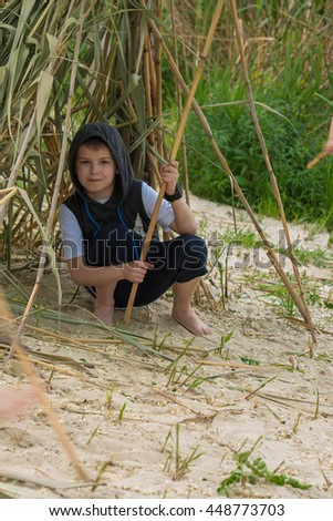 UKRAINE, KHARKOV - MAY 27, 2016: Kid is playing near the bank of the river
