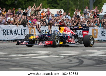 UKRAINE,KIEV - MAY 19: Scuderia Toro Rosso driver Daniel Ricciardo drive the RB7 of Red Bull Racing Fires Up the Streets of Kiev, Champions Parade, May 19, 2012 in Kiev, Ukraine - stock photo