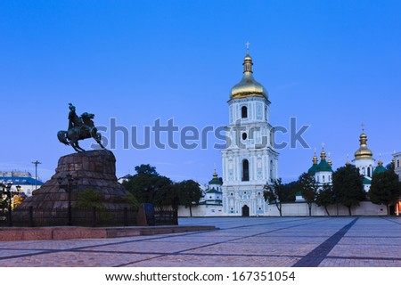 Ukraine Kiev St Sophia monastery complex and square with bell tower and Bohdan Khmelnitskiy monument at sunrise - stock photo