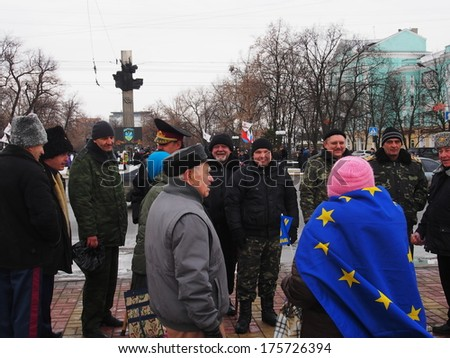 UKRAINE, LUGANS - FEBRUARY 9, 2013: An activist with the EU flag on his shoulders with a Cossack discusses guarding rally. Opposition rally in the center of Lugansk near monument of Taras Shevchenko.