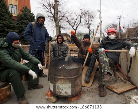 UKRAINE, LUGANSK - April 11, 2014: A group of pro-Russian activists warm themselves at bonfire next to barricades in front of entrance to Ukrainian regional office of the Security Service in Luhansk