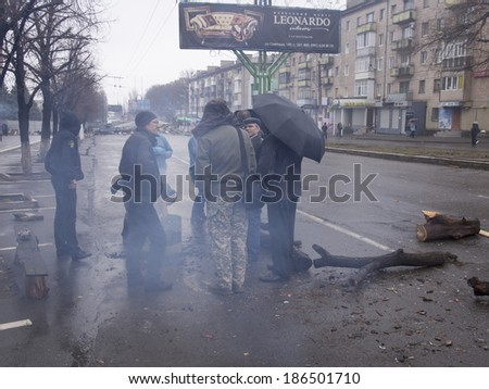 UKRAINE, LUGANSK - April 10, 2014: pro-Russian activists are heated by a fire in a steel barrel near the Ukrainian regional office of the Security Service in Lugansk