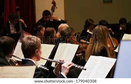 UKRAINE, LUGANSK - FEBRUARY 27,  2014: Lugansk Philharmonic Orchestra performed the Concerto No1 for piano and orchestra by Camille Saint-Saens. Conductor is Catherine Osadchaya, soloist - Irina Burgan. - stock photo